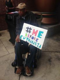 "Image of a man in a wheelchair, holding a sign that reads ""#MeBeforeEuthanasia"